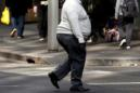 A man crosses a main road as pedestrians carrying food walk along the footpath in central Sydney